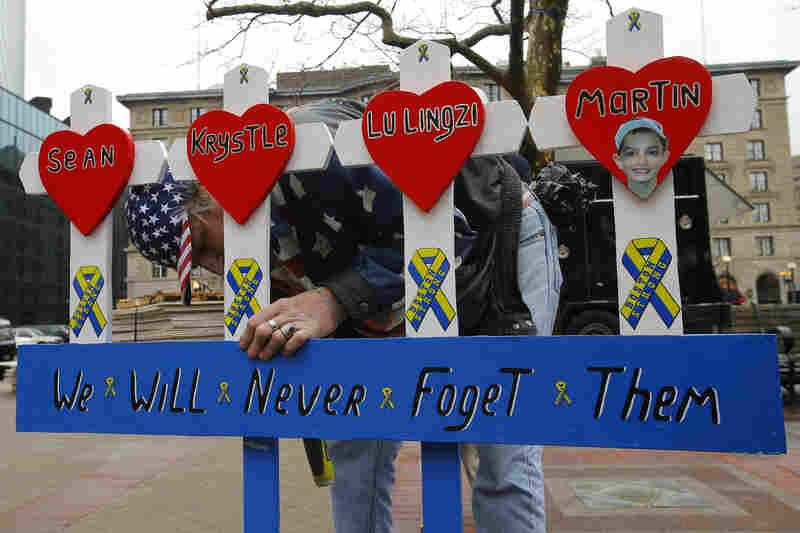 Kevin Brown puts up a hand-made memorial for victims of the 2013 Boston Marathon bombings near the race's finish line in Boston, Mass., Tuesday.