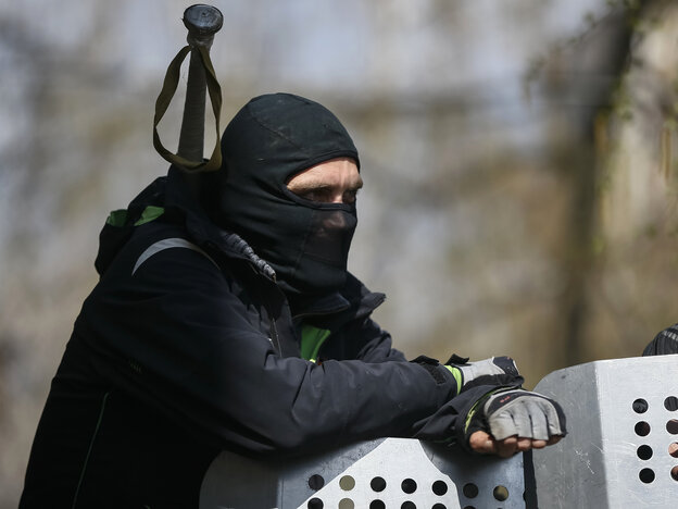 One of the pro-Russia protesters who have taken over the police headquarters in Slovyansk, Ukraine, watched from the barricades on Tuesday. Ukrainian authorities said special forces were beginning an operation against the demonstrators.