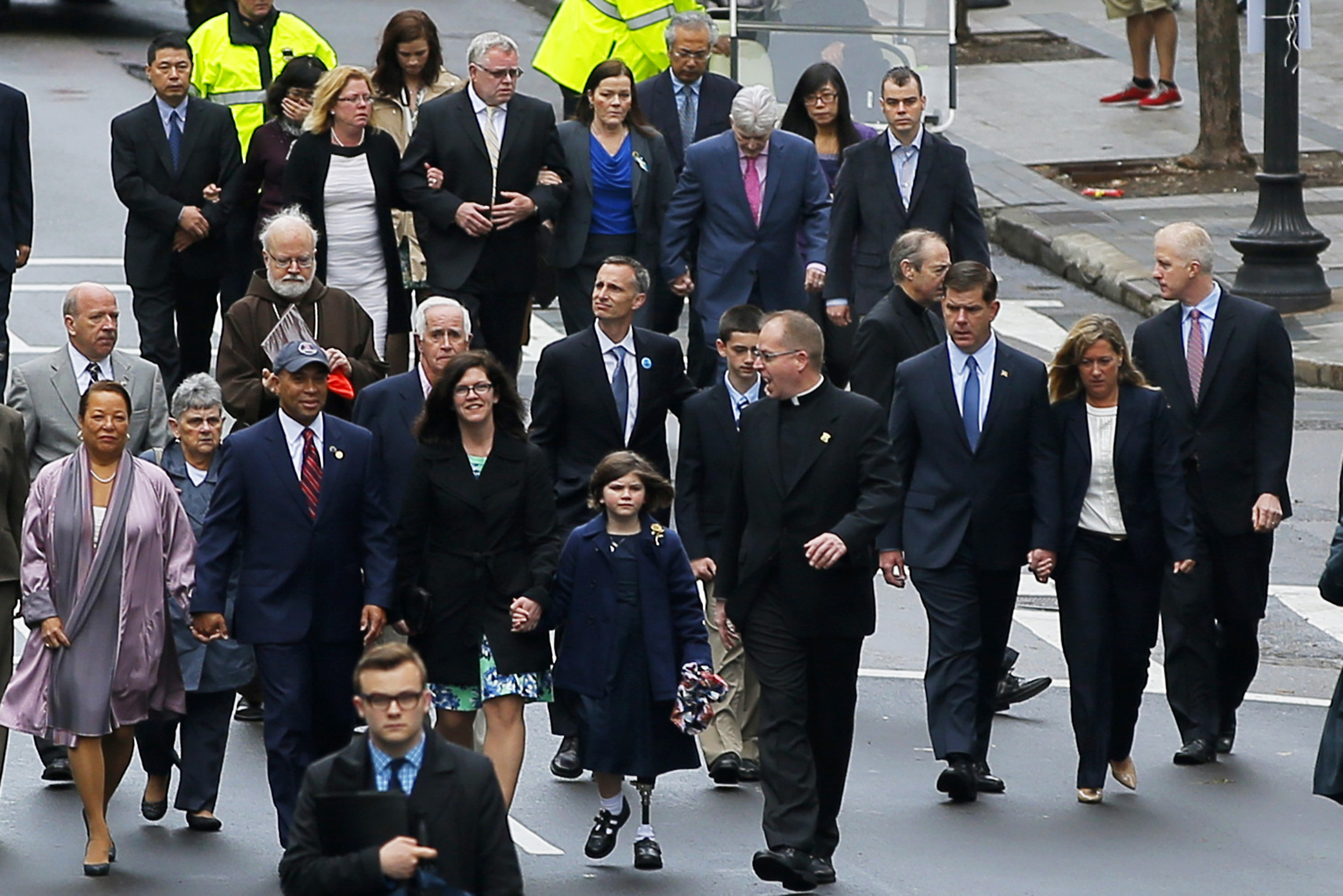 Family members of the victims of the 2013 Boston Marathon bombings walk with Massachusetts Gov. Deval Patrick (in baseball cap, L) and Boston Mayor Marty Walsh (3rd R).