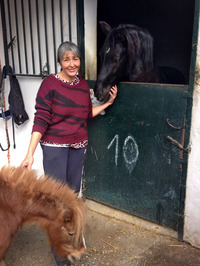 Concordia Márquez, founder of the CYD Santa Maria shelter,  poses with two horses she adopted.
