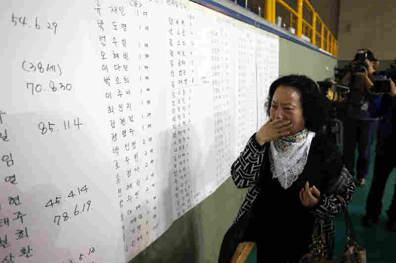 The mother of a passenger reacts as she finds her son's name on a list of survivors posted in a gym where rescued passengers gathered in Jindo.