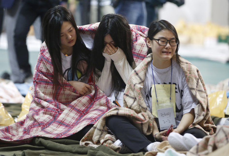Survivors huddle together at a gym. NPR's Frank Langfitt says that South Korea's coast guard reported having rescued at least 164 people before the ferry sank. (Reuters/Landov)