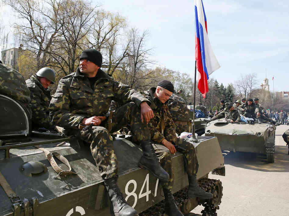 Men sit on an armored personnel carrier in Slovyansk, Ukraine, on Wednesday. A Russian flag flies from it. When some Ukrainian forces approached the city, locals say, they were persuaded to hand over their vehicles to pro-Russia protesters.