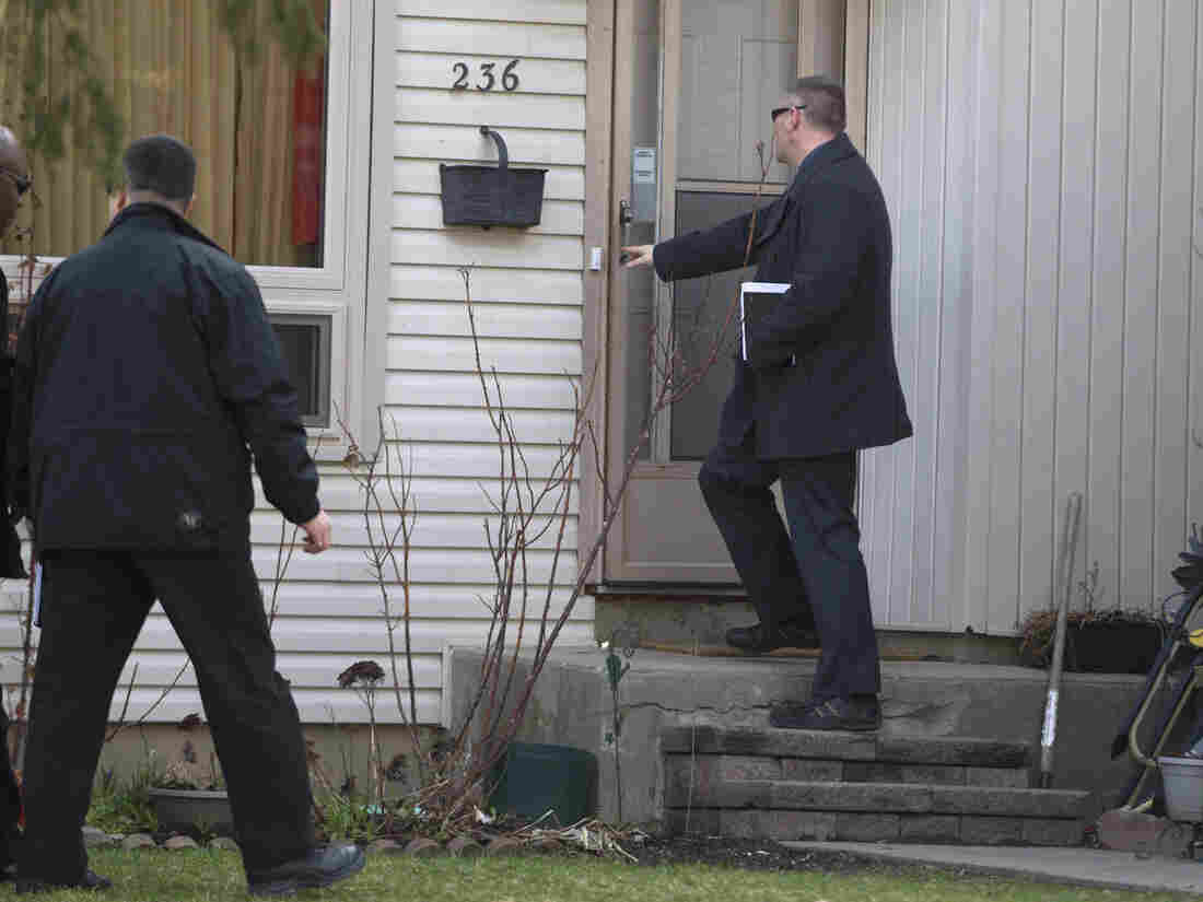 """Royal Canadian Mounted Police investigators canvass the London, Ontario, neighborhood around the home of Stephen Solis-Reyes, who has been charged in connection with exploiting the """"Heartbleed"""" bug."""