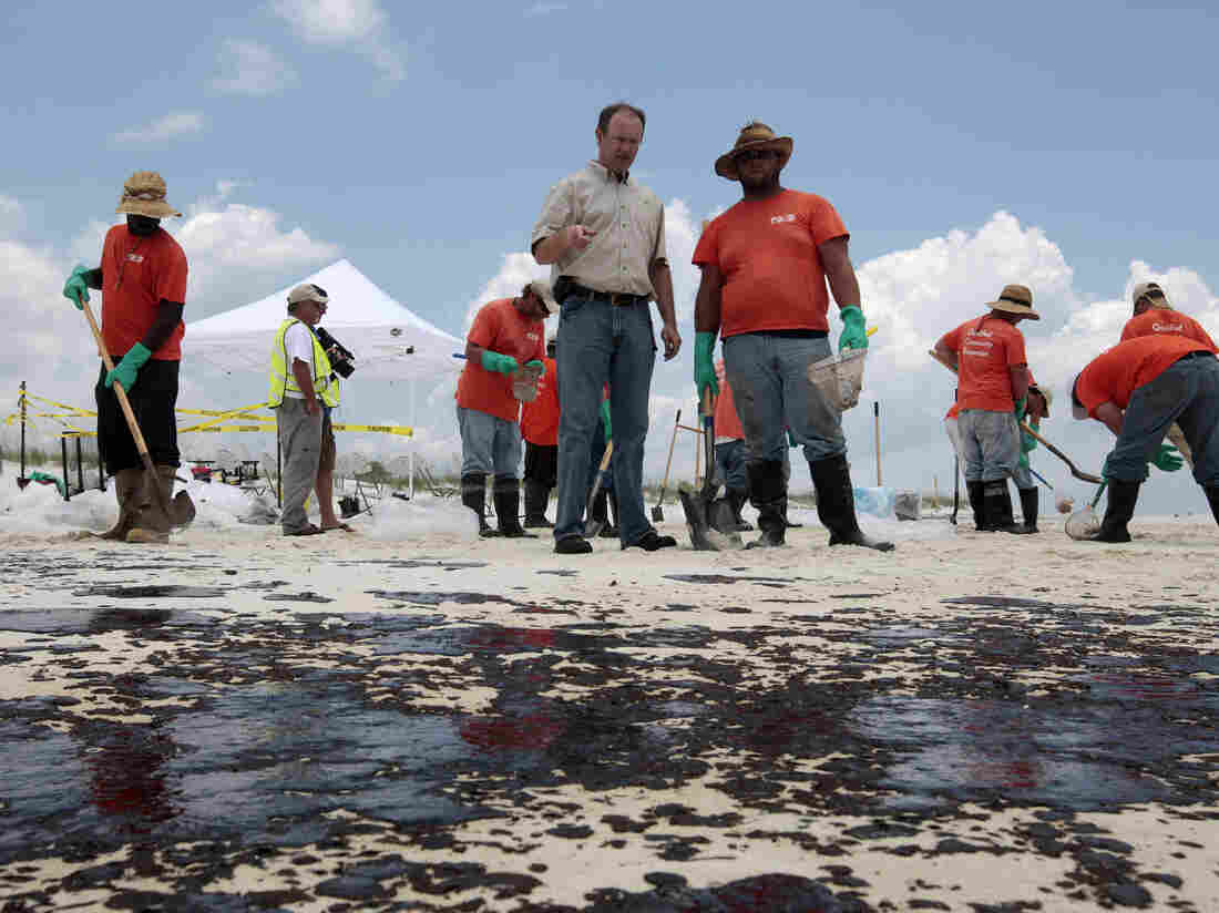 BP Mobile Incident Commander Keith Seilhan talks with oil cleanup workers in Gulf Shores, Ala., in July 2010. Seilhan has settled with SEC regulators who say he avoided $100,000 in stock and options losses by trading on inside information related to the spill.