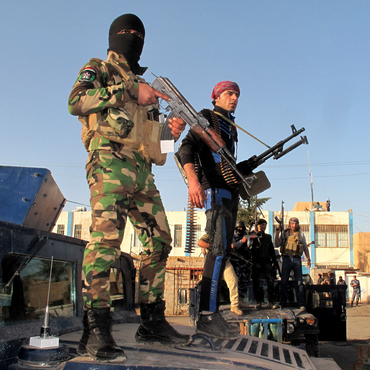Tribesmen and Iraqi police forces hold a position in a street of the city of Ramadi, west of the capital Baghdad, on Jan. 30, during a military operation against anti-government fighters.