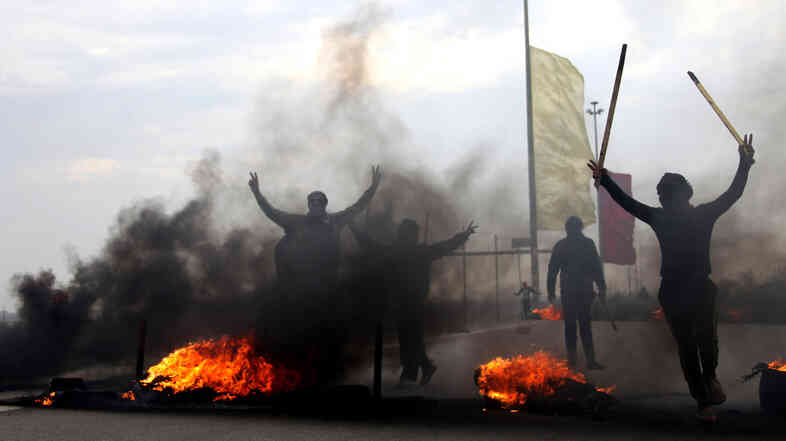 Iraqi Sunni masked protesters burn tires to block the main highway to Jordan and Syria, outside Fallujah, Iraq, on Dec. 30, 2013. Violence has returned to Iraq's Anbar province, with discontented ordinary Sunnis joining forces with al-Qaida-linked militants battling the Iraqi government.
