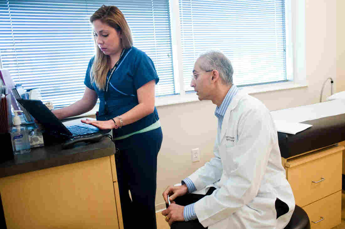 Medical scribe Connie Gayton keeps the electronic records, allowing orthopedic surgeon Devesh Ramnath to focus on his patients.