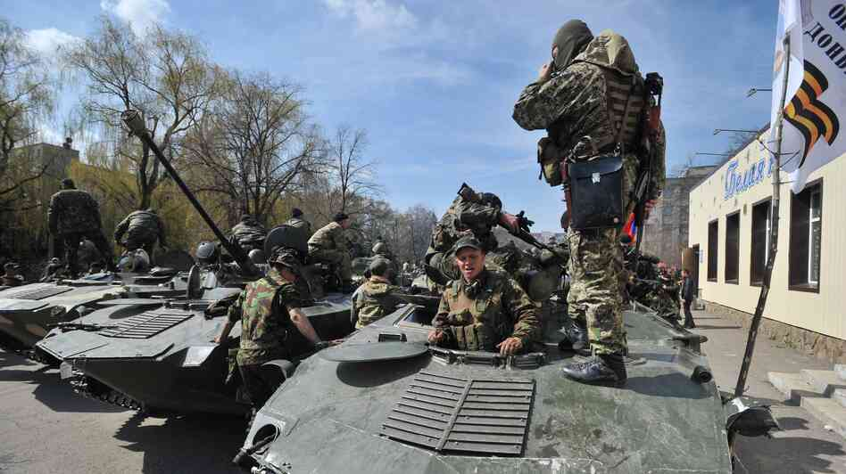 Armed men wearing military fatigues gathered on armored personnel carriers Wednesday in the eastern Ukrainian city of Slovyansk, where they and other pro-Russia gunmen took control of some key locations.
