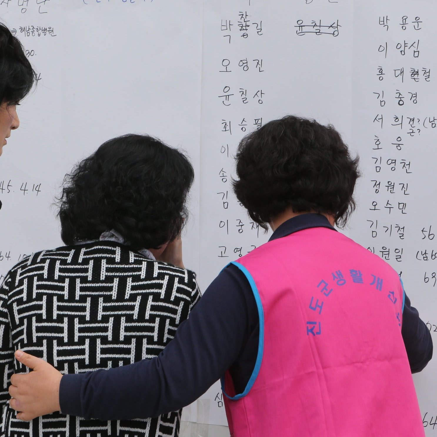 Family members of passengers on a South Korean ferry that sank look at lists of survivors on Wednesday.