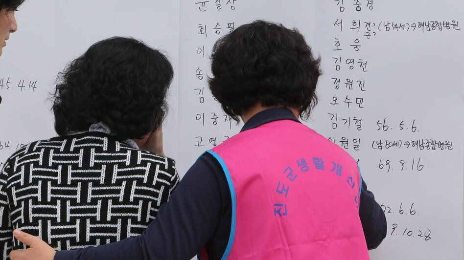 Family members of passengers on a South Korean ferry that sank look at lists of survivors on Wednesday. (EPA/Landov)