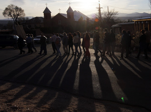 The faithful follow penitentes — lay members of a Catholic brotherhood — to Mass at Holy Cross Catholic Church in Santa Cruz, N.M., on Holy Thursday in 2013.
