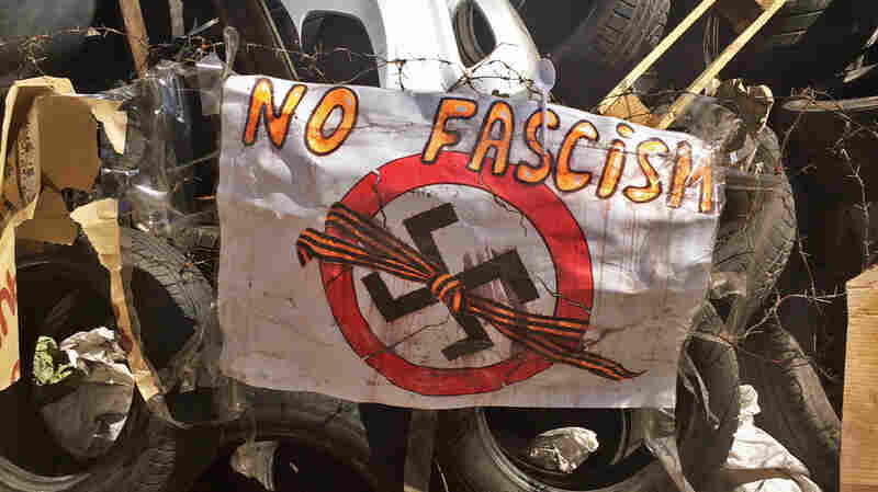 An anti-fascist sign hangs on the barricade outside an occupied government building in Donetsk.