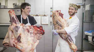 Legume Chef Trevett Hooper and butcher Tyler Mossman with large beef cuts in the restaurant's kitchen.