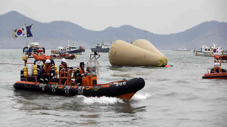 South Korean rescue team boats sail around buoys which mark the area of a sunken ferry as they try to search passengers believed to have been trapped inside.
