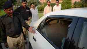 A Pakistani policeman points to the damaged car that was carrying Pakistani journalist Hamid Mir when he was attacked in Karachi Saturday. Mir is reportedly out of immediate danger.