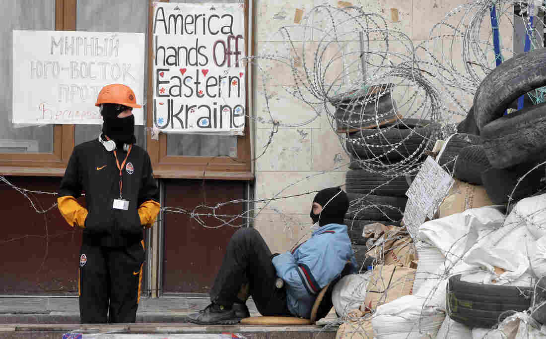 """Masked pro-Russian activists guard a barricade at an occupied regional administration building in Donetsk, Ukraine, Saturday. Ukraine says it is suspending an """"anti-terrorist"""" operation for Easter."""