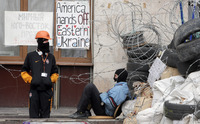 Masked pro-Russian activists guard a barricade at an occupied regional administration building in Donetsk, Ukraine, Saturday. Ukraine says it is suspending an