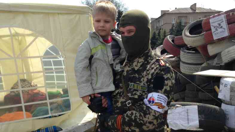 A masked guard holds a young boy at a barricade outside a building being held by pro-Russia forces in Donetsk, Ukraine.