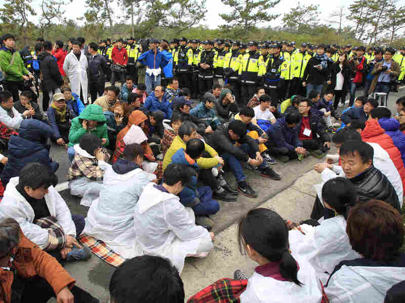 Relatives of missing passengers sit on a road Sunday as police block their march toward the presidential house to protest the government's rescue operation in a port in Jindo, South Korea.