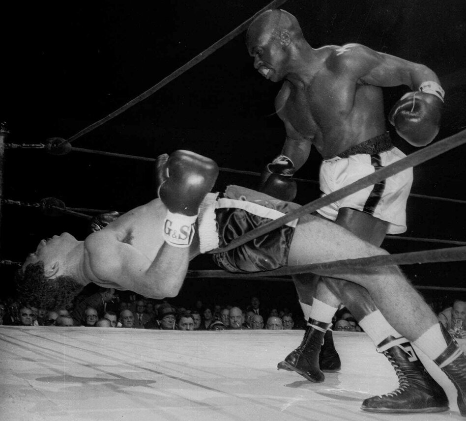 Rubin Carter of Paterson, N.J. watches Florentino Fernandez of Cuba fall through the ropes during their 1962 fight, after Fernandez was knocked out in the first round at New Yorsk's Madison square Garden. Carter has died at age 76.