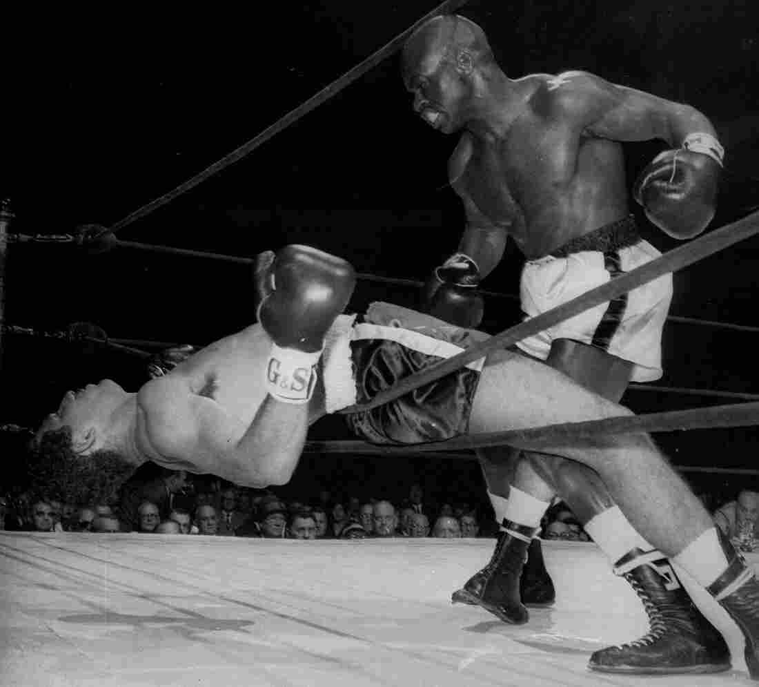 Rubin Carter of Paterson, N.J. watches Florentino Fernandez of Cuba fall through the ropes during their 1962 fight, after Fernandez was knocked out in the first round at New York's Madison square Garden. Carter has died at age 76.