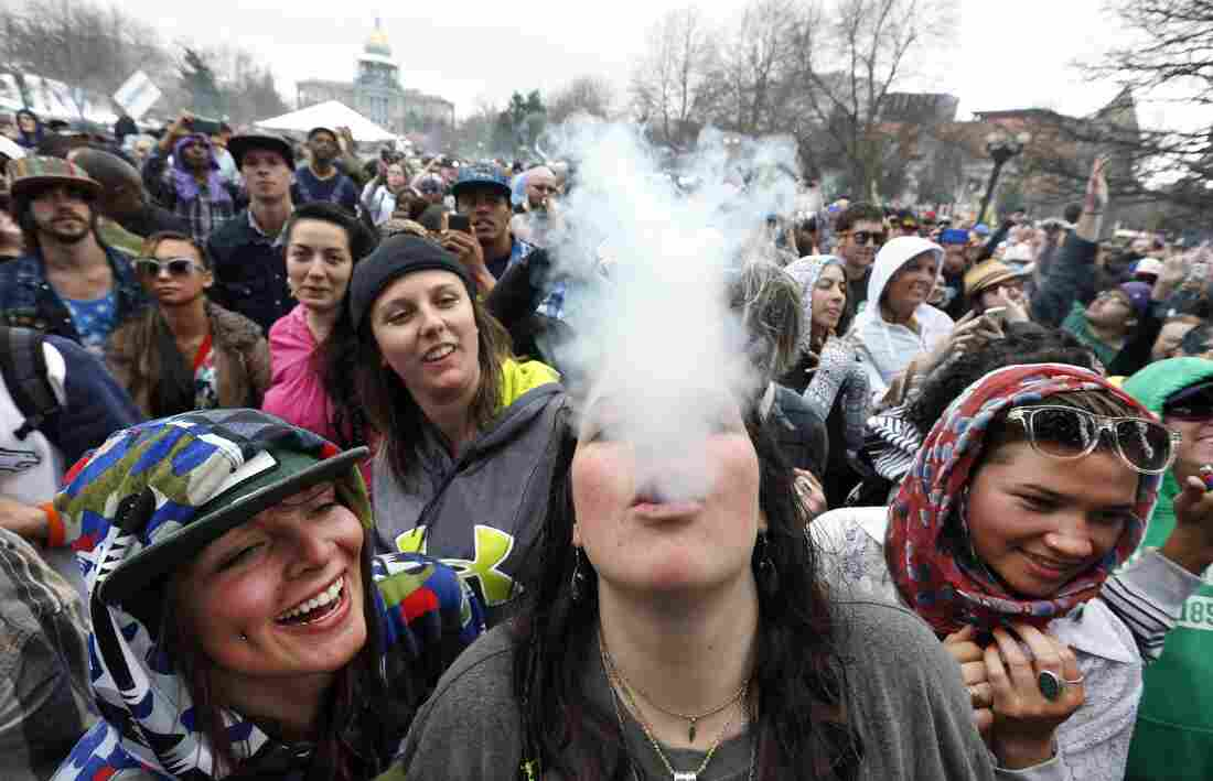 With the Colorado state capitol in the background, Cannabis Cup attendees dance and smoke pot at the annual 4/20 marijuana festival in Denver.