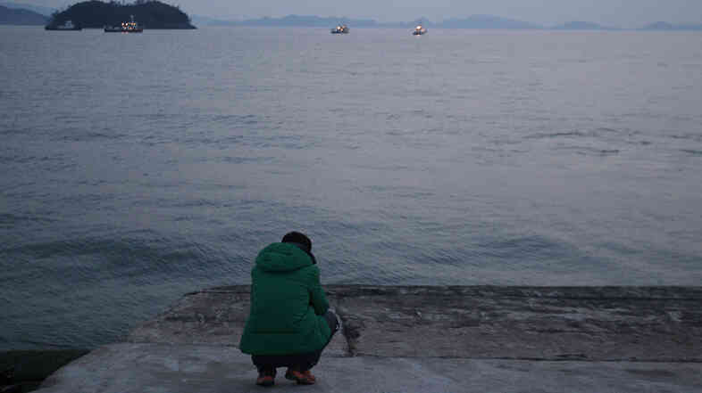 A relative waits for word of missing passengers of a sunken ferry in Jindo, South Korea. A newly released transcript depicts a scene of confusion on the stricken ferry as it sank.
