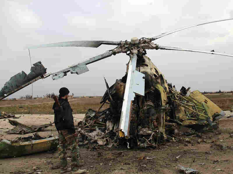 Rebel fighters inspect the wreckage of a Syrian army helicopter after the Islamic State of Iraq and Syria, or ISIS, allegedly destroyed it in March in the northern Syrian city of Aleppo.