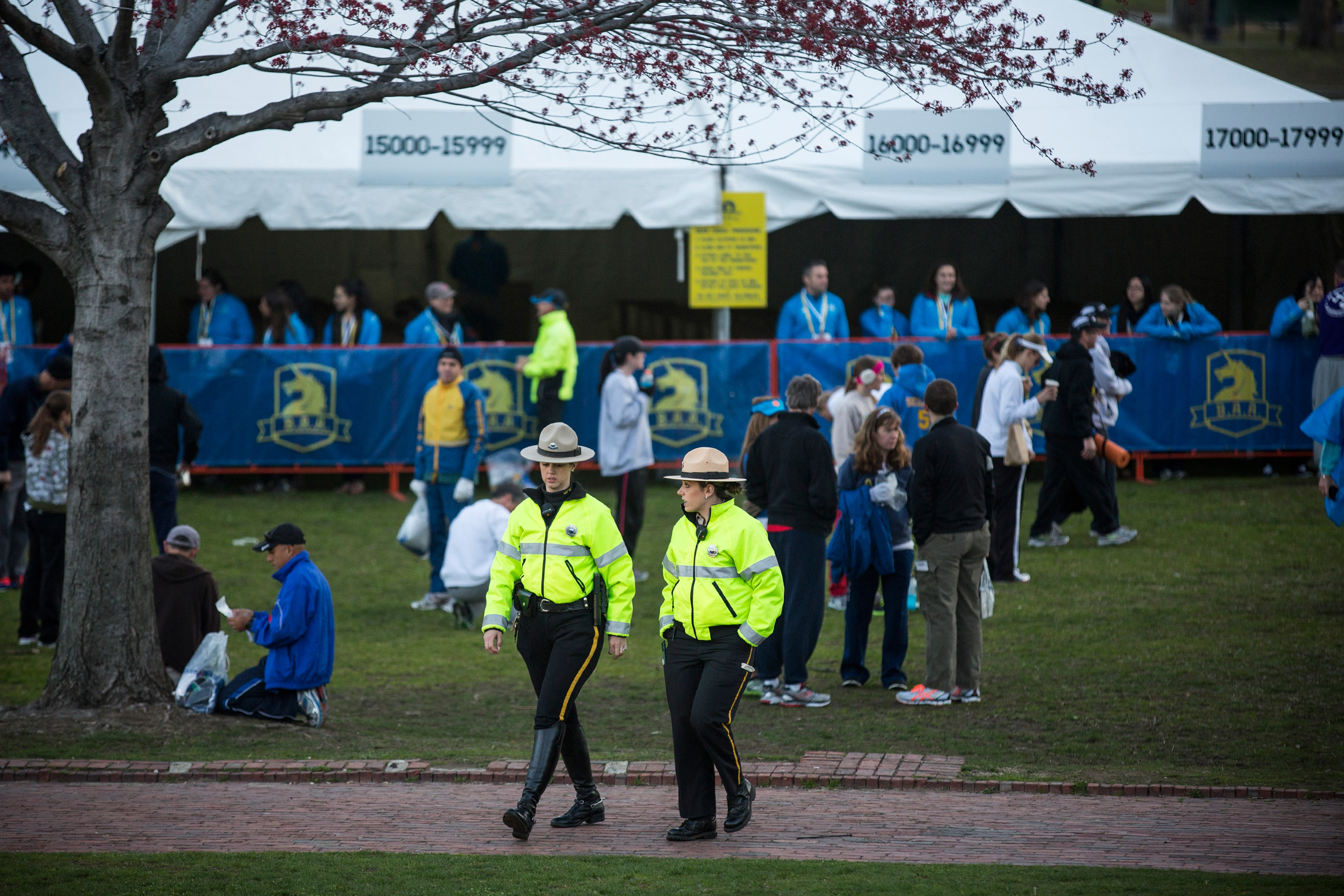 Police officers monitor the area as runners prepare for the marathon in Boston Common. A year after the terrorist bombings, a far greater security presence is clearly visible.