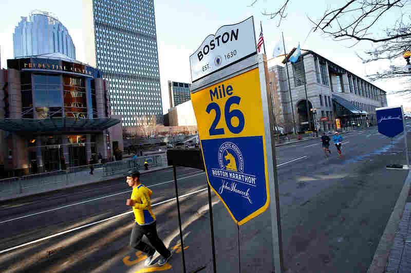 A few people run along Boylston Street near the 26-mile marker prior to the start of the marathon.