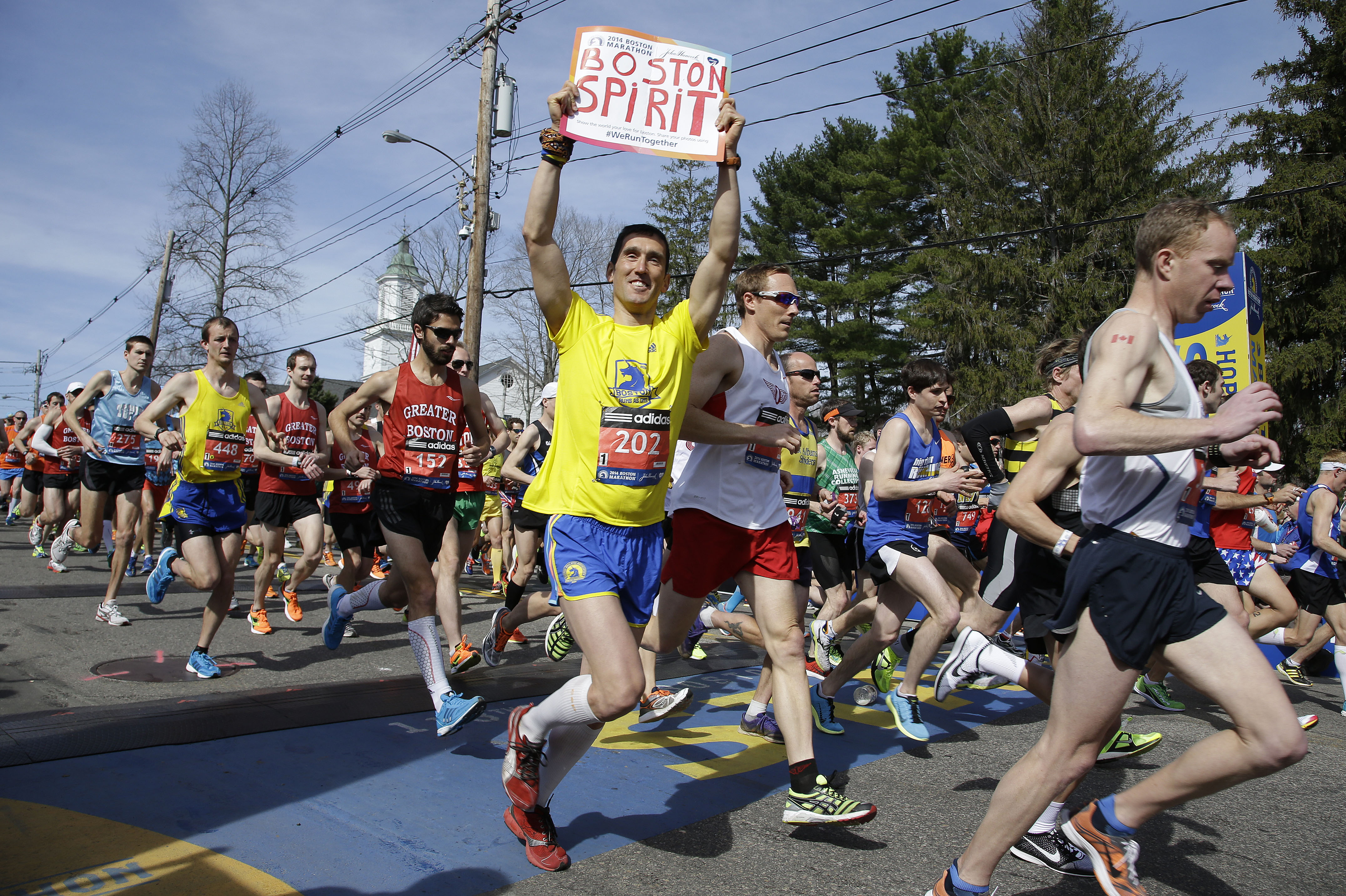 Runners in the first wave of 9,000 cross the start line of the 118th Boston Marathon on Monday in Hopkinton, Mass. Around 36,000 athletes will run the marathon in the first running of the race since last year's bombing attack.