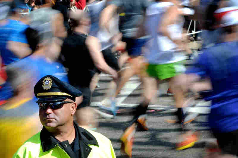 Runners go by at the starting section of the marathon in Hopkinton, Mass.