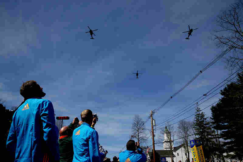 Volunteers look on during a flyover by the Massachusetts Army National Guard before the start of the marathon in Hopkinton.