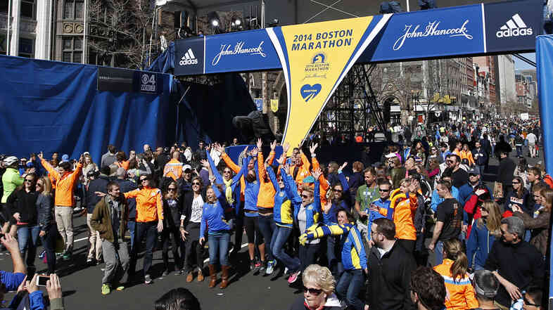 Runners, their friends and family members posed Sunday for photos at the finish line of the Boston Marathon, which is being run on Monday.