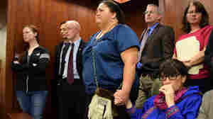 Just before Alaska's Senate voted to make 20 Alaska Native languages official state languages alongside English, Rep. Charisse Millett (seated) held hands with Liz Medicine Crow. Left of them is Rep. Jonathan Kreiss-Tomkins, who introduced the bill.