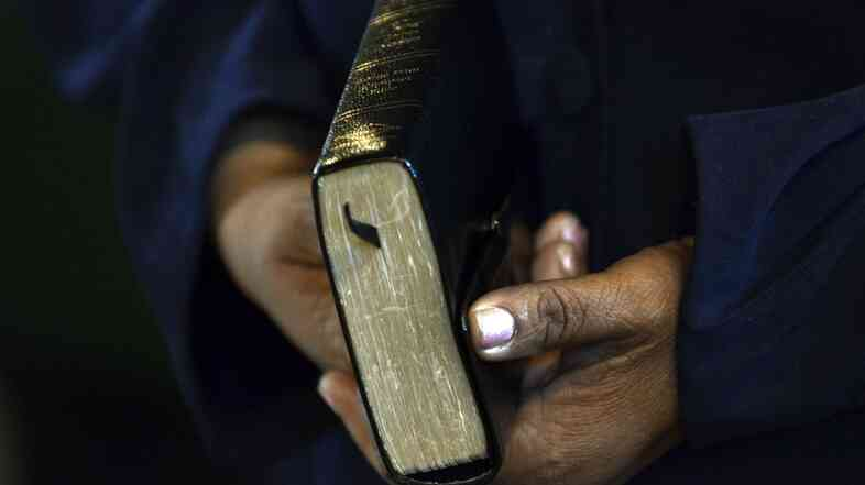 A parishioner holds the Holy Bible during a service. A Louisiana bill that would have made the Bible the state's official book has been withdrawn.
