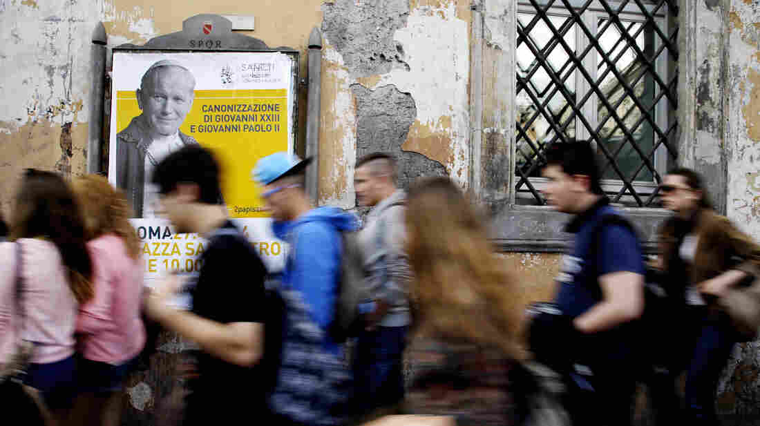 Tourists walk past a poster of Pope John Paul II on April 13 in Rome.
