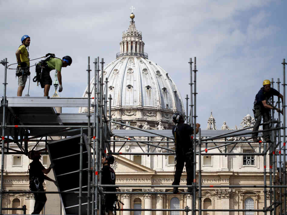 Workers stand on scaffolding in front of St. Peter's Basilica in Rome on Tuesday. This Sunday, Pope Francis will canonize the late Pope John Paul II, who reigned from 1978 to 2005, and Pope John XXIII, the pontiff fro