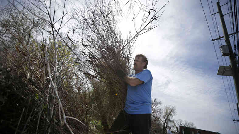 Volunteer Tom Strain carries debris from an empty lot as part of an Earth Day cleanup effort in Camden, N.J. The Earth Day events celebrated on April 22 promote a sustainable and clean environment.
