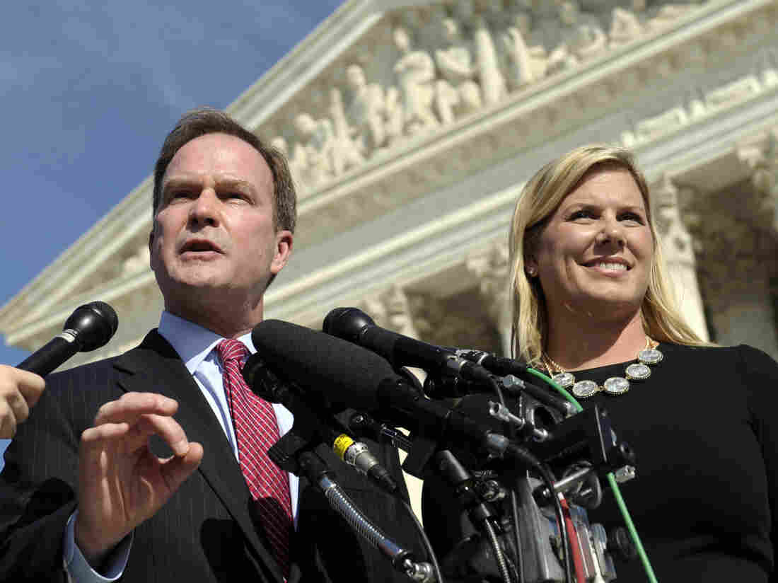 Michigan Attorney General Bill Schuette speaks to reporters after arguing the case before the U.S. Supreme Court in October. He's with XIV Foundation CEO Jennifer Gratz, who was a plaintiff in a lawsuit against the University of Michigan's affirmative action policy.