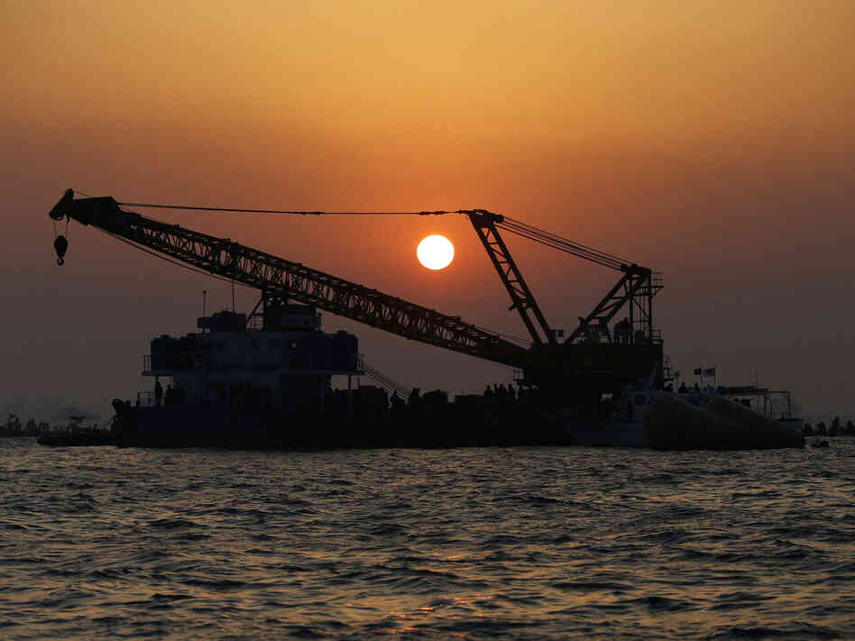 As the sun set on Tuesday, recovery operations continued at the site of the ferry disaster off South Korea's southern coast.