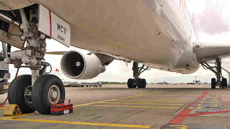 The underbelly of a Boeing 767, the type of plane on which a teenager stowed away by hiding inside one of the rear wheel wells (in background) during a flight from California to Hawaii. He survived.