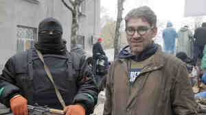 In a photo taken earlier this month, U.S. reporter Simon Ostrovsky stands with a pro-Russian gunman at a seized police station in the eastern Ukrainian town of Slovyansk. Ostrovsky has reportedly been seized by the pro-Russian insurgents.