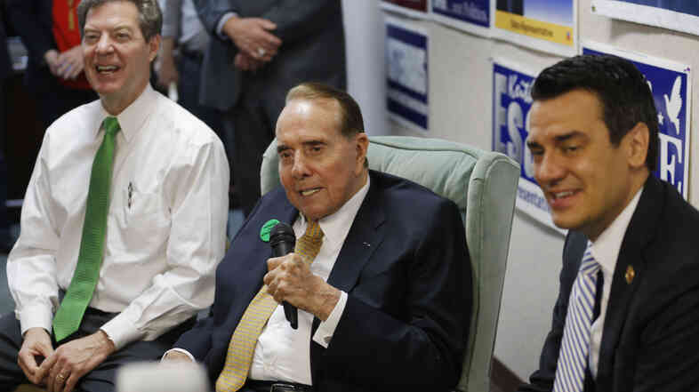 Former Kansas Sen. Bob Dole, center, takes questions while seated between Gov. Sam Brownback, left, and Rep. Kevin Yoder, right, during a visit to the Johnson County Republican headquarters in Overland Park, Kan., on Monday.