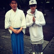 Justin Bieber poses next to an unidentified man at Yasukuni Shrine in Tokyo.