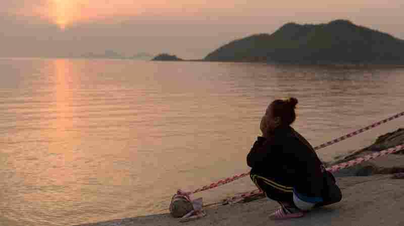 As the sun set Wednesday in Jindo, South Korea, a woman kept watch