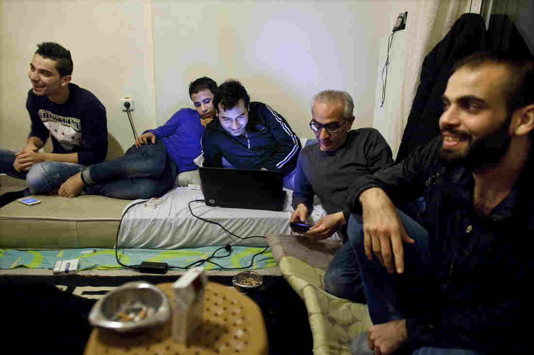 Fadi (from left), Muhammad, Abo Firas, Muwafak and Kefah wait for dinner in a one-room apartment in Athens, Greece. Eight refugees lived in the apartment; all of the men were neighbors back home in Syria.