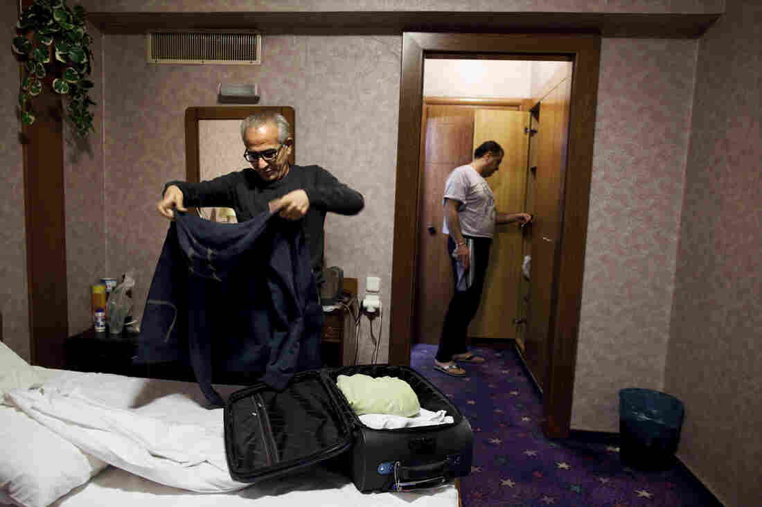Muwafak packs a new suitcase with his few belongings, in the hotel room he shares with Hassan, in Athens, Feb. 10. Muwafak and Hassan hope ultimately to receive asylum in Germany.