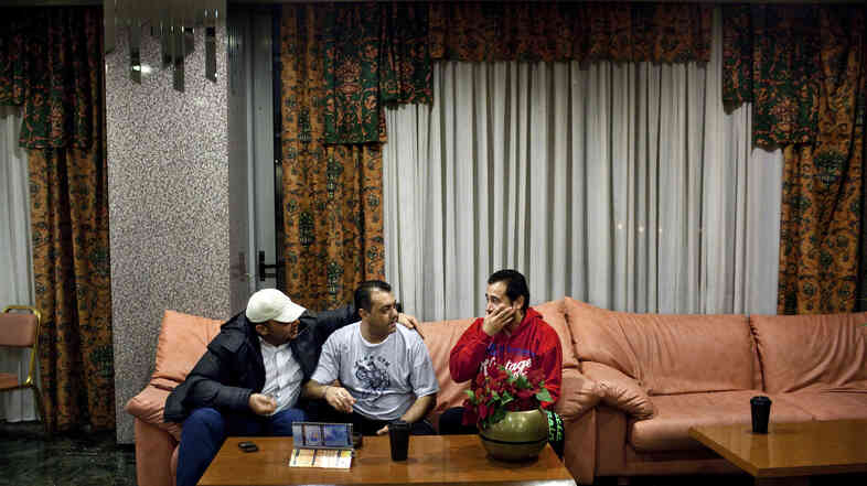 Abu Ghassan (from left), Hassan and Sobhy sit in the lobby of a hotel in Athens, Greece, that blocks out at least 40 rooms each month for Syrian refugees and gives them a discount, on Feb. 11. Though the Syrians have a safe haven at the hotel, Greece as a whole has not been as welcoming.